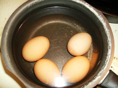 Four brown shelled eggs, hardboiled